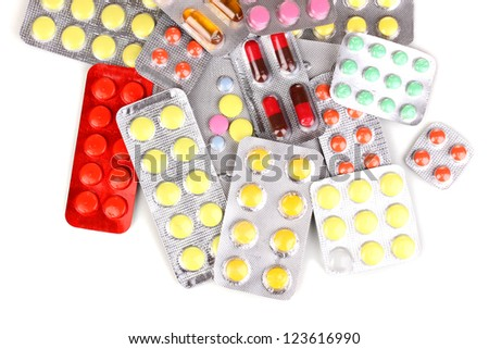 Capsules and pills packed in blisters isolated on white close-up
