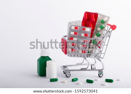Capsules and tablets in shop trolley on a white background. Buy medicine. Medicine concept.