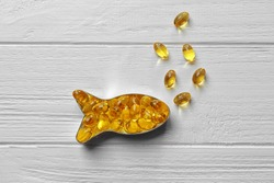 Capsules of cod liver oil arranged in a fish shape on white wooden background