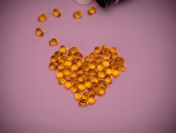 Capsules of cod liver oil arranged in a heart shape on pink background. Heart Shaped Fish Oil. Close up. Omega 3 capsules. Top view, copy space. Health care concept