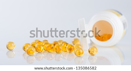 Capsules of fish oil spilled out open container #135086582
