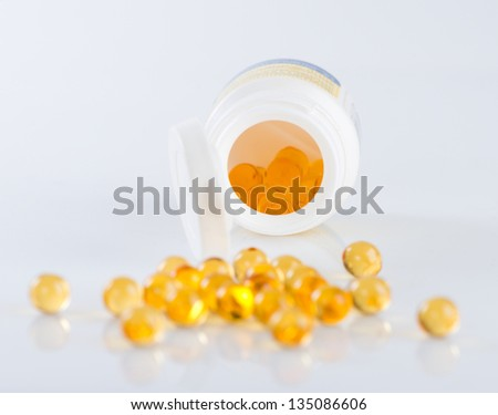 Capsules of fish oil spilled out open container #135086606