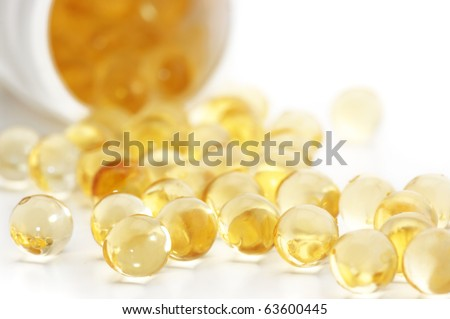 Capsules of fish oil spilled out open container on white background.