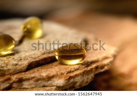 Capsules Omega 3. Soft gel capsules on the surface of natural stone. Сlose up fish oil on gold background. Сoncept of health. Омега 3. gold pattern Сток-фото ©