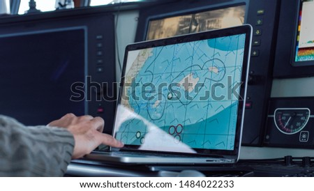 Captain of Commercial Fishing Ship Surrounded by Monitors and Screens Working with Sea Maps in his Cabin. Сток-фото ©