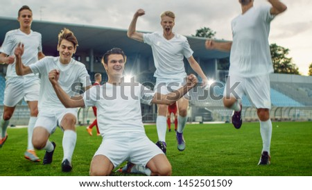 Captain of the Soccer Team Stands on His Knees Celebrates Awesome Victory, Makes YES Gesture Champion Team Joins Him. Successful Happy Football Players Celebrate Victory.