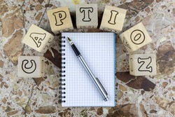 Caption concept with notebook and pen below arched alphabet letters on wooden cubes on a marbled stone background with copyspace. Flat lay