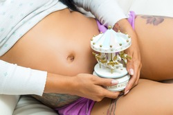 caption of pregnant belly sitting down and hands holding a small carousel