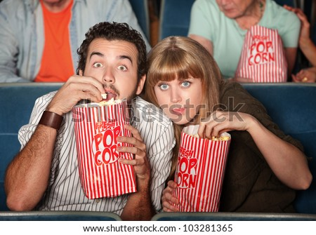 Captivated couple  with popcorn bags in a theater