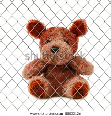Captured bear toy. Cute little teddy bear behind the wire fence over a white background. Child abuse concept.