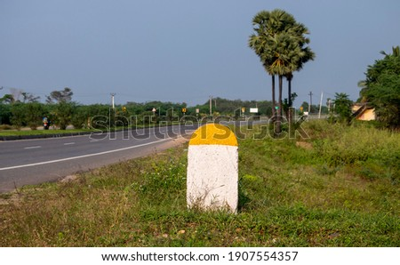 Captured Real Photo of Plain Yellow and White Milestone with National Highway Road and green plants Background which can be used for writing Kilometre numbers on it found in Tamilnadu South India Asia Foto stock ©