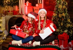 Capturing a happy moment. happy small girls has xmas mood. Enjoying New Year party. santa children spend holiday. Opening Christmas present. winter shopping sale kid store. Little Christmas magic.