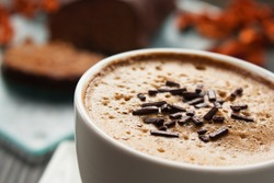 Capuccino in white cup  with chocolate sprinkles and cake in the back.
