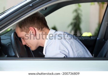 Car accident man with his head on steering wheel