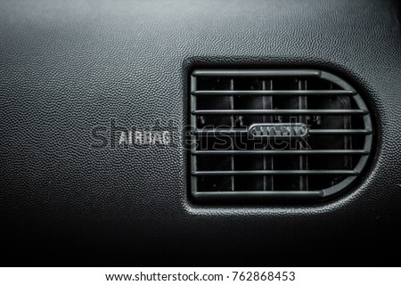 Car air ventilation. Airbag text next to it. Dark car itnerior background #762868453