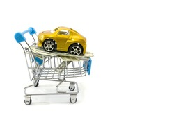 Car and dollar in a shopping trolley on a white background. Car as a gift. Buy a car. Copy of space