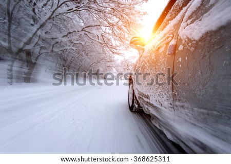 Car and falling snow in winter on forest road with much snow.(Motion blur) #368625311