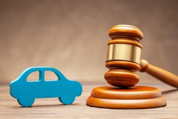 Car and judge gavel on brown background. Concept of selling a car by auction or accident sentence.