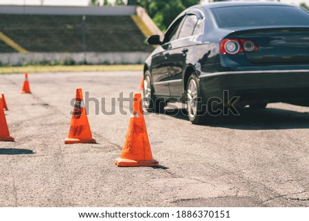 Car and traffic cones, driving school concept. Old orange plastic cone in place for car driving training, extreme driving school at autodrome. Stadium for safe driving training. School training car.