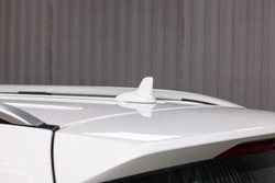 Car antenna on the roof of a white car for signaling gps, bluetooth and television