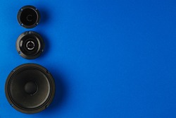 Car audio. Car speakers, bass speaker and midrange speaker lie in a row on a blue background. Copy space