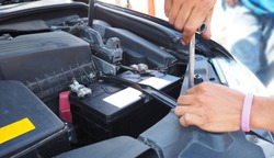 Car battery ,fitting a car battery with wrench and checking some parts of the engine.
