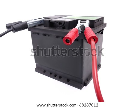 Car battery with two jumper cables clipped to the terminals shot over white