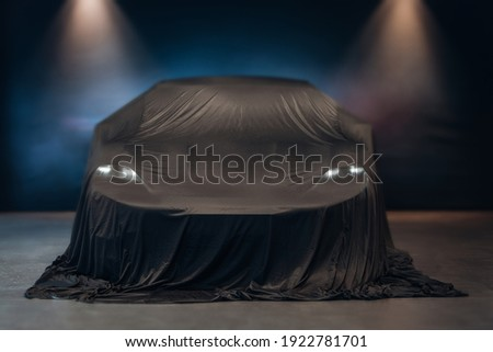 Car before official presentation, covered by the clothю Car under the tissue at the autoshow