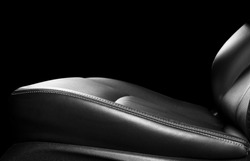 Car black leather seat isolated on black background. Part of leather car seat details with stitching. Perforated leather seats. Black perforated leather. Car detailing. Black and white