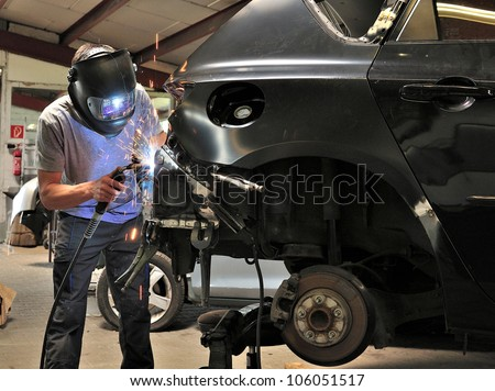 Car body worker welding car body.