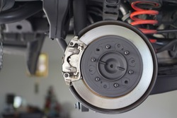 Car brake part at garage,car brake disc without wheels.Suspension of car in car service. Close up.