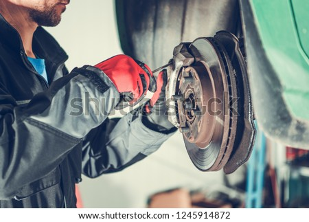 Car Brakes Servicing by Caucasian Vehicle Mechanic in His 30s. Automotive Industry.   Сток-фото ©
