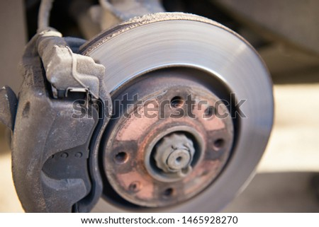 Car brakes. Work in tire shop. Brake disc after removing the wheel. #1465928270