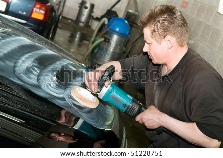 car care work with machine polisher at service station