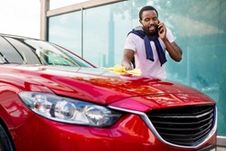 Car celaning and polishing outdoors. Portrait of young African man cleaning his car with a cloth outdoors at self service car wash, and talking by his smartphone