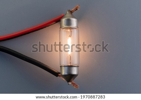 Car classic halogen bulb. Filament, glass and metal, high energy consumption. Gray background. interior lighting. energized, working condition. Lights up Stock photo ©