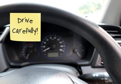 Car console panel with handwritten stick note DRIVE CAREFULLY , concept of self remind driver to drive carefully or safety first