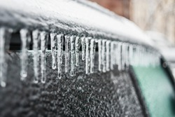 Car covered with ice and icicles after freezing rain. Ice covered car window close up. Bad winter weather, ice storm in November Vladivostok. Winter frosty scenes.