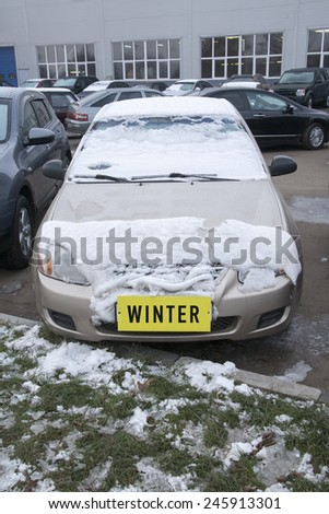 car covered with snow on the street with a yellow \'winter\' label instead of the number