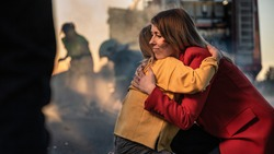 Car Crash Traffic Accident: Injured Young Girl Reunites with Her Loving Mother. In the Background Fire engine and Courageous Paramedics and Firemen Save Lives