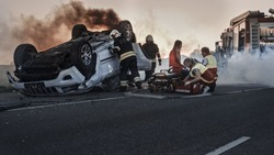 Car Crash Traffic Accident: Paramedics and Firefighters Rescue Injured Trapped Victims. Medics give First Aid to a Female Passenger. Firemen Use Hydraulic Cutters Spreader to Open Vehicle