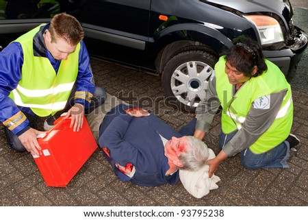 Car crash victim being helped by paramedics (the sleeve badges have been replaced by a non existing logo)