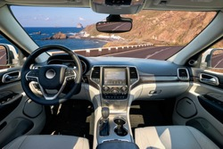 Car dashboard and steering wheel. The interior of a modern luxury SUV type car.Kokpit trimmed with leather and decorated with precious wood