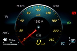 Car dashboard panel including speedometer with red needle, odometer, fuel gauge, lane assist icon, gear position indicator and dipped beam headlights. Modern car digital LCD instrument cluster.