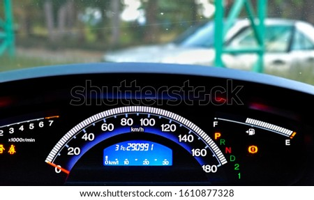 Car dashboard showing instrument and controls information like speedometer, fuel gauge, turn indicators, gearshift position indicator, seat belt warning light, parking-brake warning light.