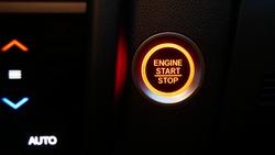 Car dashboard with focus on red engine start stop button, car interior details. button engine start and engine stop, Car engine push start stop button ignition remote starter.