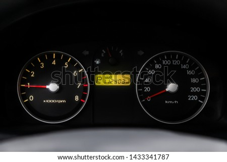 Car dashboard wuth red backlight: Odometer, speedometer, tachometer, fuel level, water temperature and more. Modern car interior: parts, buttons, knobs