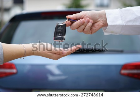 car dealer gives the customer the car keys with car in background