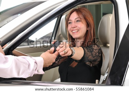 Car dealer giving keys of a new car to happy red head customer - a series of BUYING A NEW CAR images.