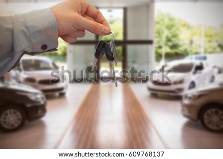 Car dealer giving keys to a customer against cars parked